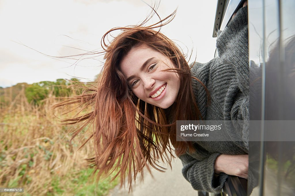 Young woman with head out of car window : Stock-Foto