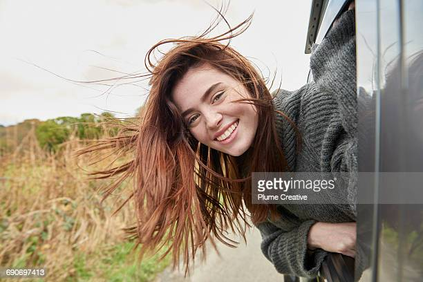 Young woman with head out of car window