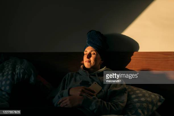 young woman with head wrapped in a towel lying in bed at home - einfaches leben stock-fotos und bilder