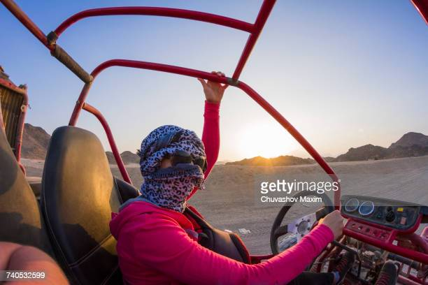 Young woman with head wrapped in scarf driving beach buggy in desert, Hurghada, Al Bahr al Ahmar, Egypt