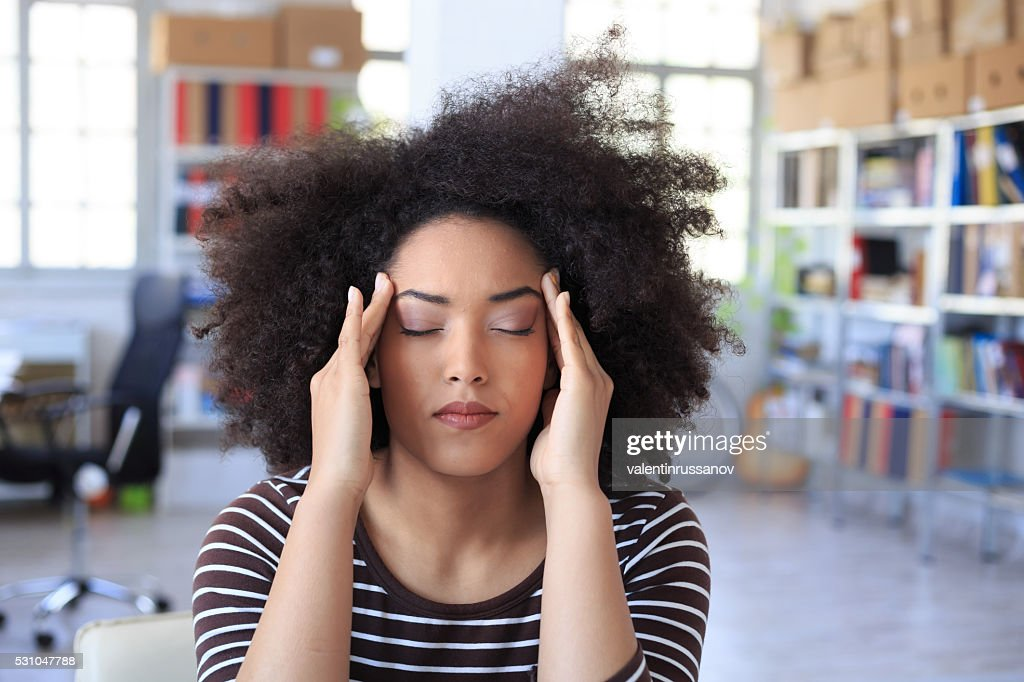 Young woman with headache at the office : Stock Photo