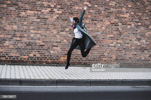 Young woman with headphones and backpack jumping in the air in front of brick wall