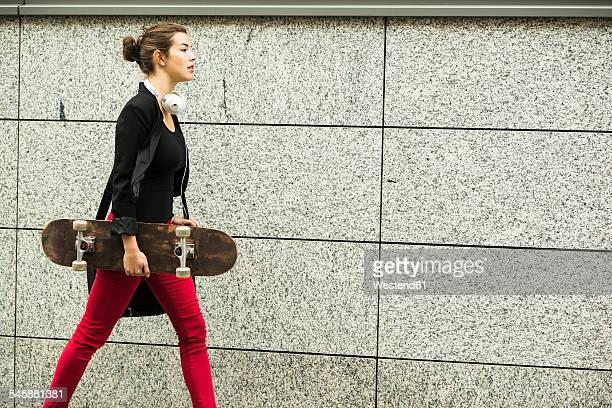 Young woman with headphones and skateboard walking in front of grey wall