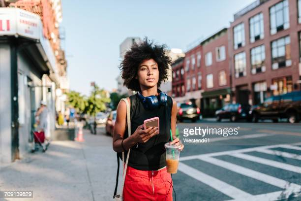 Young woman with headphones and smart phone crossong street in Brooklyn, carying take away drink
