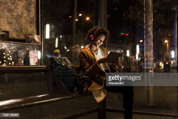 Young woman with headphones and tablet waiting at the tram stop