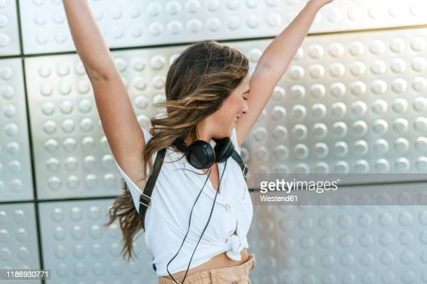 young woman with headphones around neck dancing with raised arms, silver background - silver blouse stock pictures, royalty-free photos & images