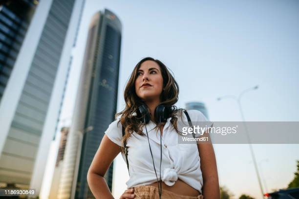 young woman with headphones around neck, skyscrapers in the background - low angle view stock pictures, royalty-free photos & images