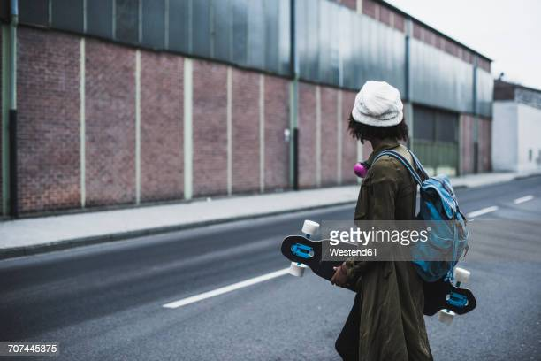 Young woman with headphones, backpack and skateboard on the street