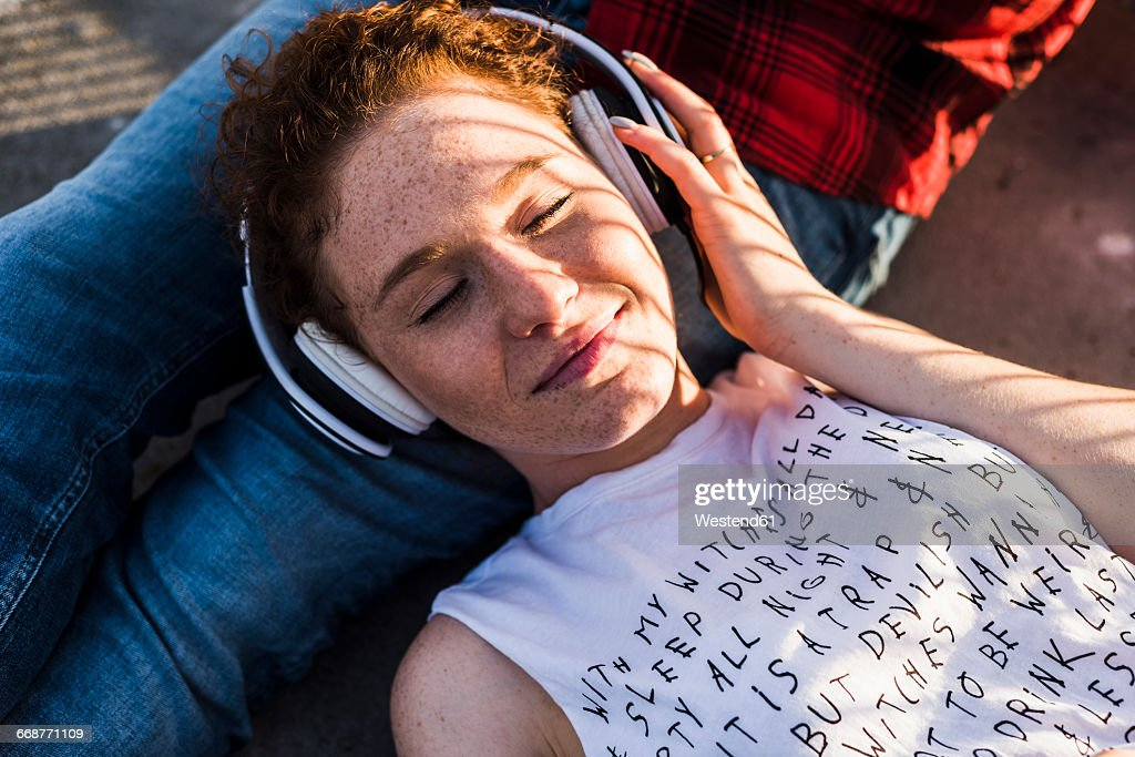 Young woman with headphones lying on boyfriend's lap : Stockfoto