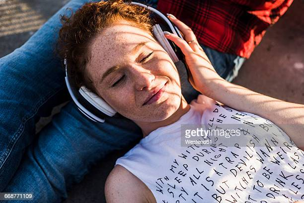 young woman with headphones lying on boyfriend's lap - zuhören stock-fotos und bilder