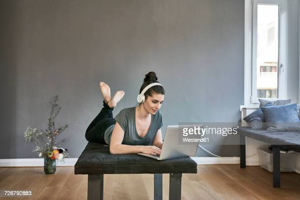 Young woman with headphones lying on lounge using laptop