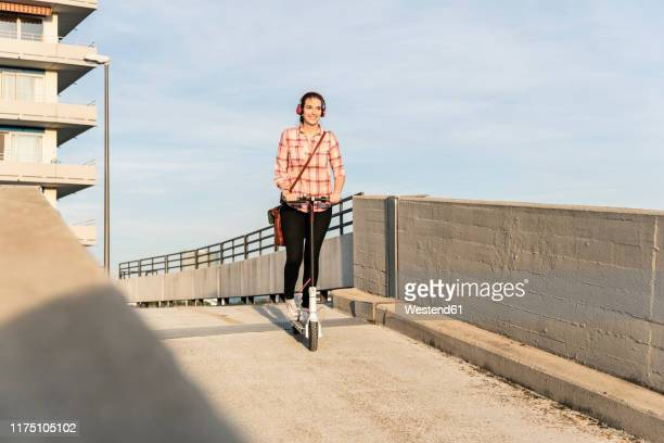 young woman with headphones riding electric scooter on parking deck - down blouse stock pictures, royalty-free photos & images