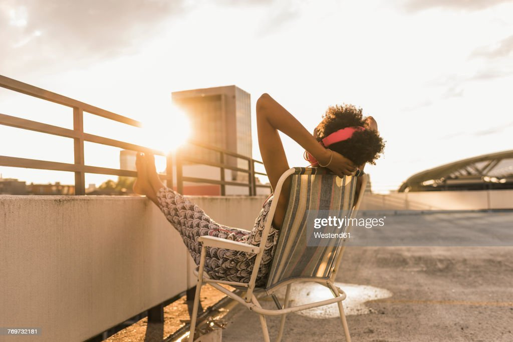 Young woman with headphones sitting on rooftop : Stock-Foto