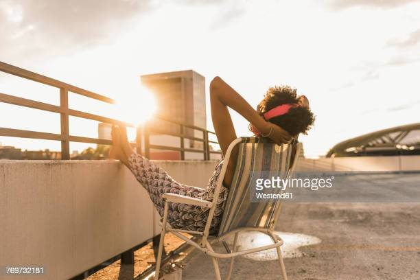 young woman with headphones sitting on rooftop - taking a break stock photos and pictures