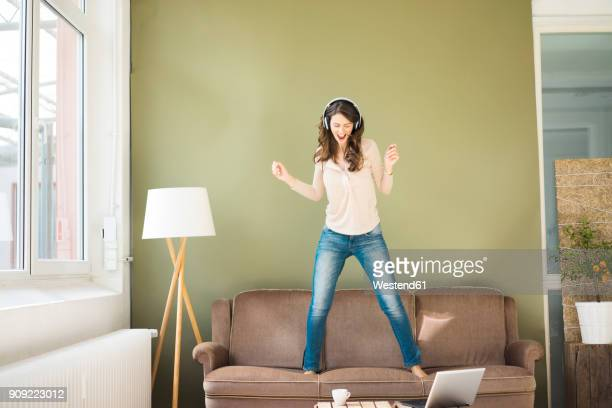 young woman with headphones standing on couch screaming and dancing - dancing stock-fotos und bilder