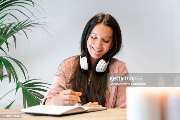young woman with headphones to listen to music hanging around her neck while she writes in a notebook with a happy expression - candle stock pictures, royalty-free photos & images