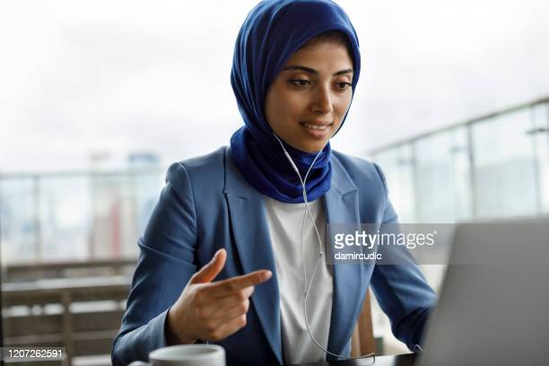 young woman with headphones working on laptop - middle east stock pictures, royalty-free photos & images