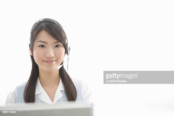 Young woman with headset looking at camera