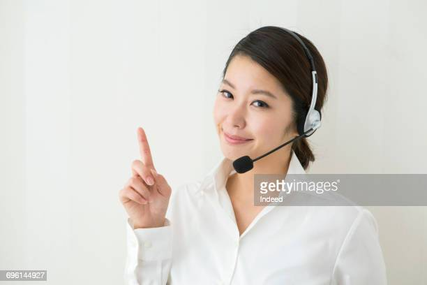 Young woman with headset pointing with her finger