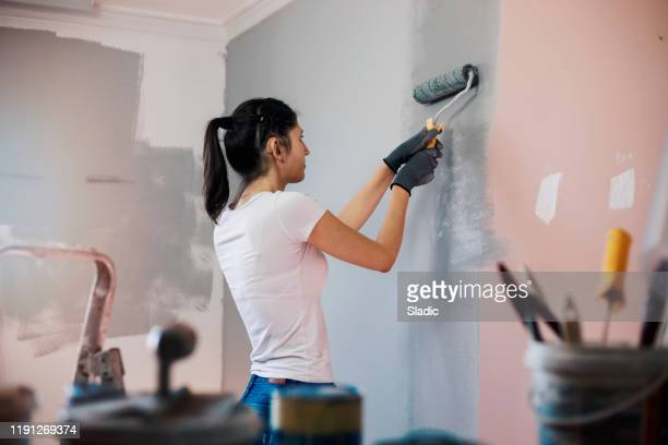 young woman with hearing aid painting walls - decoration stock pictures, royalty-free photos & images
