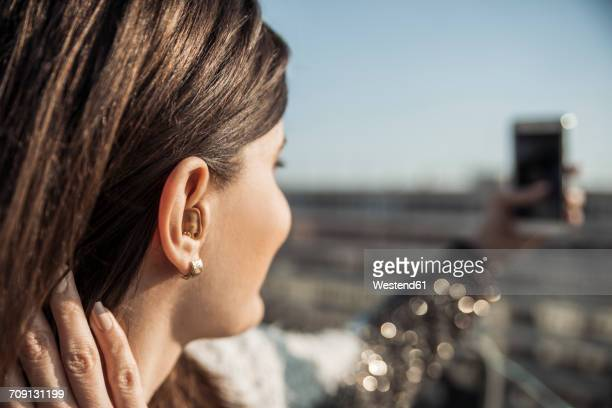 Young woman with hearing aid taking selfie with smartphone