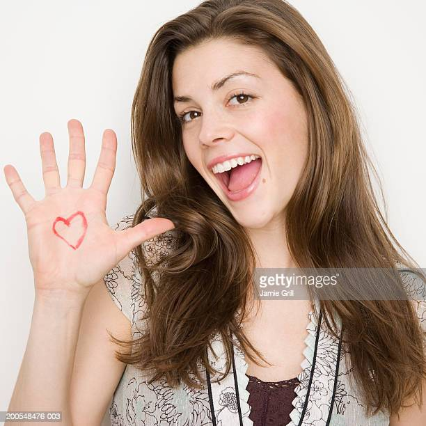 Young woman with heart drawn on hand, smiling, portrait, close-up