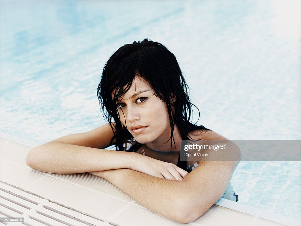 Young Woman With Her Arms Crossed at the Edge of a Swimming Pool : Stock Photo