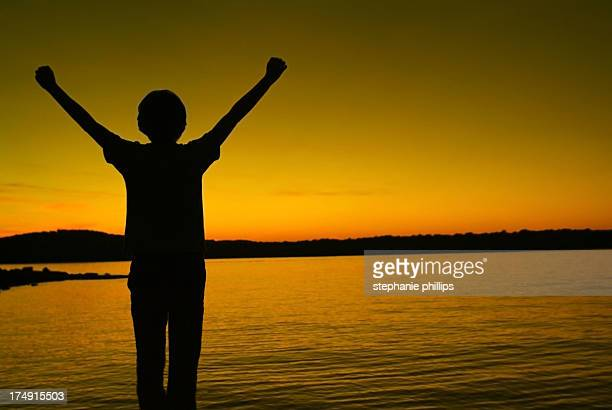 Young Woman with her Arms Raised in Celebration at Sunset