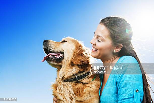 Junge Frau mit Ihrem Hund auf dem klaren Himmel.