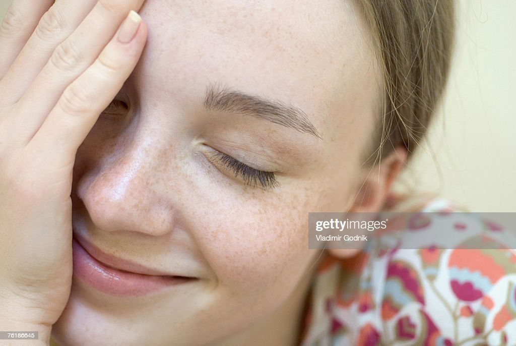 A young woman with her eyes closed and hand over her face : Stock Photo