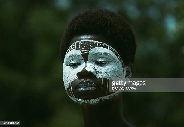 A young woman with her face painted waiting to be excised Ivory Coast