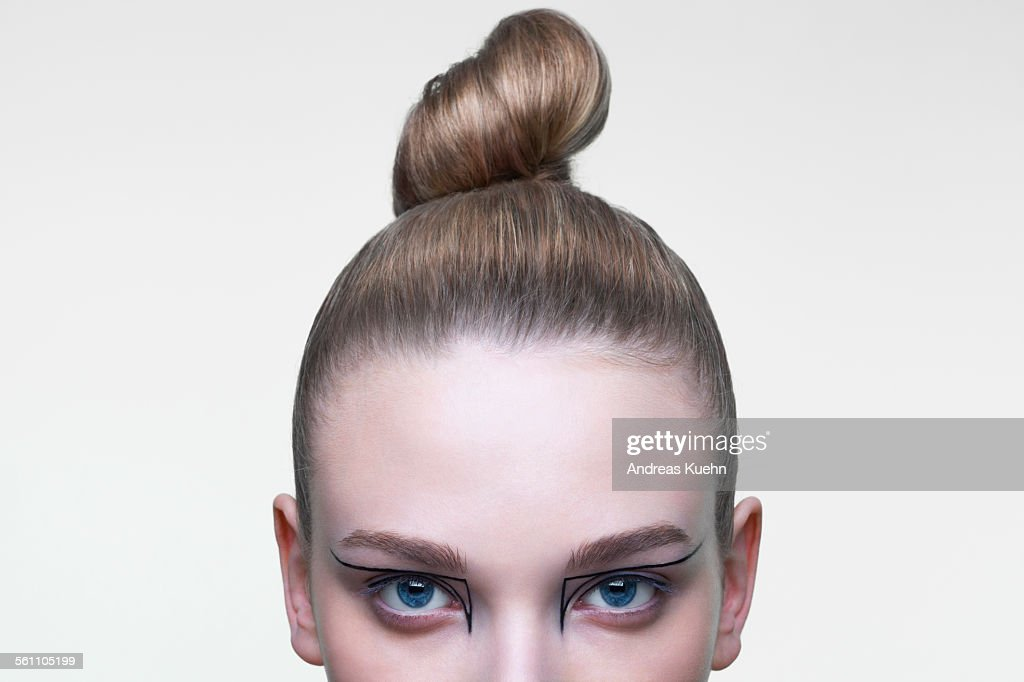 Young woman with her hair in a tight bun, cropped. : Stock Photo