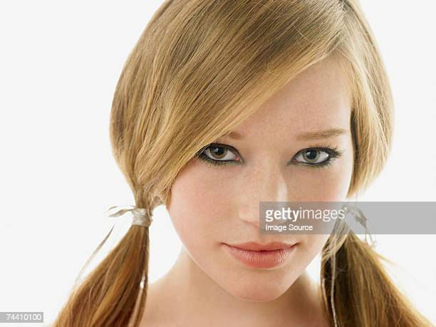 若い女性は彼女の髪を二つに結んだ髪
