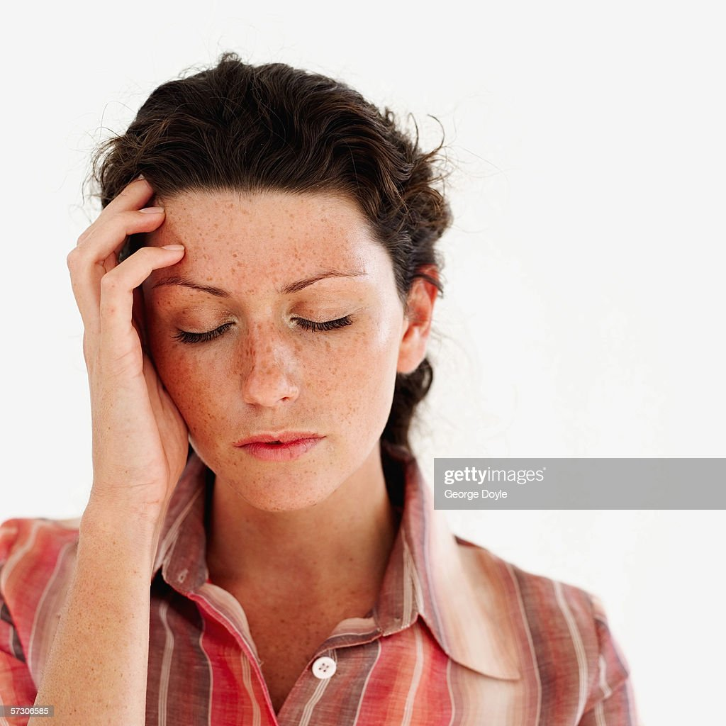 Young woman with her hand on her head and eyes closed : Stock Photo
