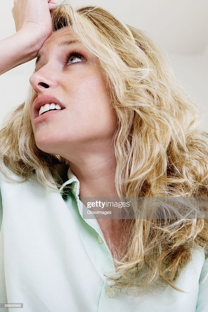 Young woman with her hand on her head : Stock Photo