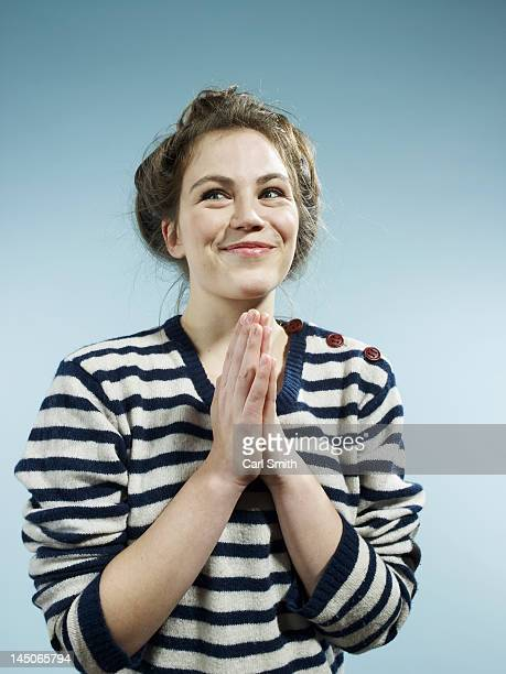 a young woman with her hands together with a look of excited hope - suplicar imagens e fotografias de stock