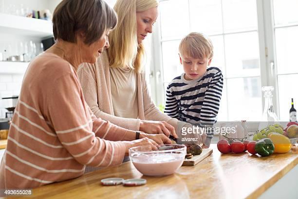 Junge Frau mit ihrer Mutter und Sohn Küche Essen