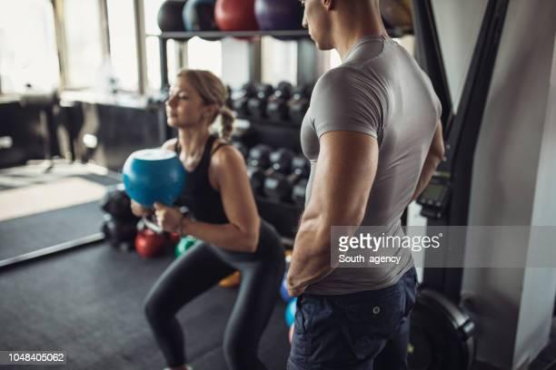 jonge vrouw met haar personal trainer in de sportschool - individualiteit stockfoto's en -beelden
