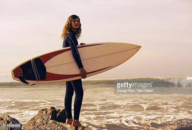 Young Woman With Her Surfboard At The Beach