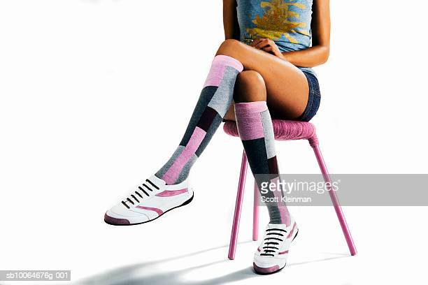 Young woman with high socks sitting against white background, low section