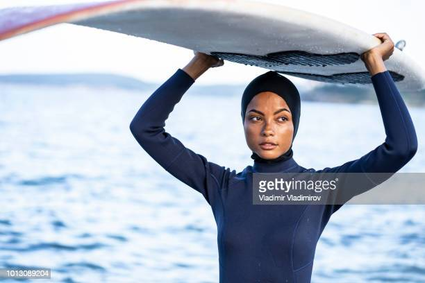 young woman with hijab carrying surfboard on beach - muslim woman beach stock photos and pictures