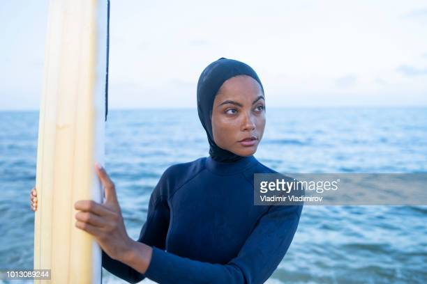 young woman with hijab holding surfboard on beach - muslim woman beach stock photos and pictures