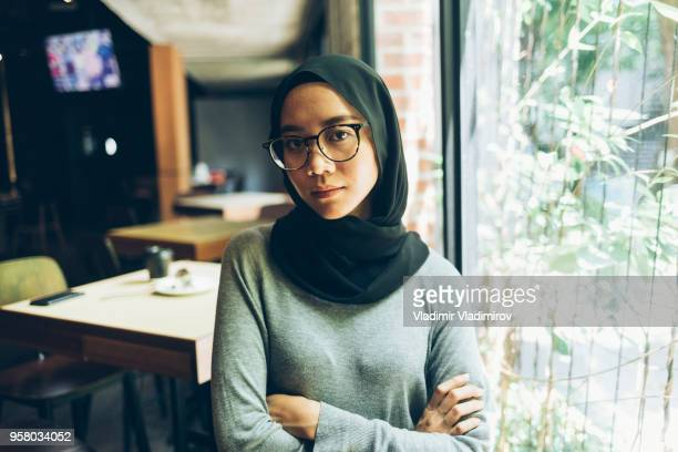 young woman with hijab standing arms crossed in cafe - religious dress stock photos and pictures