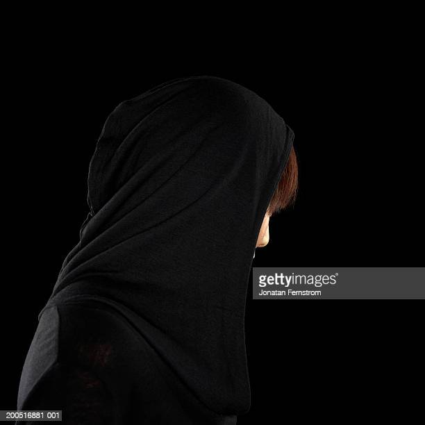 Young woman with hood against black background