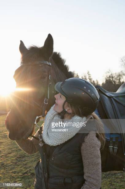 young woman with horse at backlight - riding hat stock pictures, royalty-free photos & images
