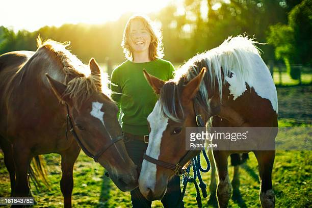 Young Woman With Horses In Pasture
