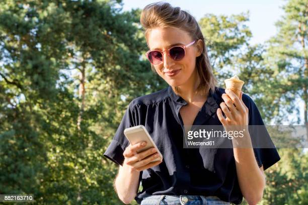 young woman with ice cone using smartphone - china: through the looking glass bildbanksfoton och bilder