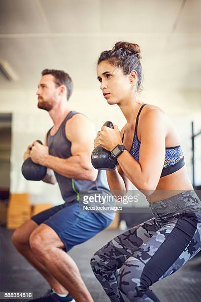 Young woman with instructor lifting kettlebells in gym