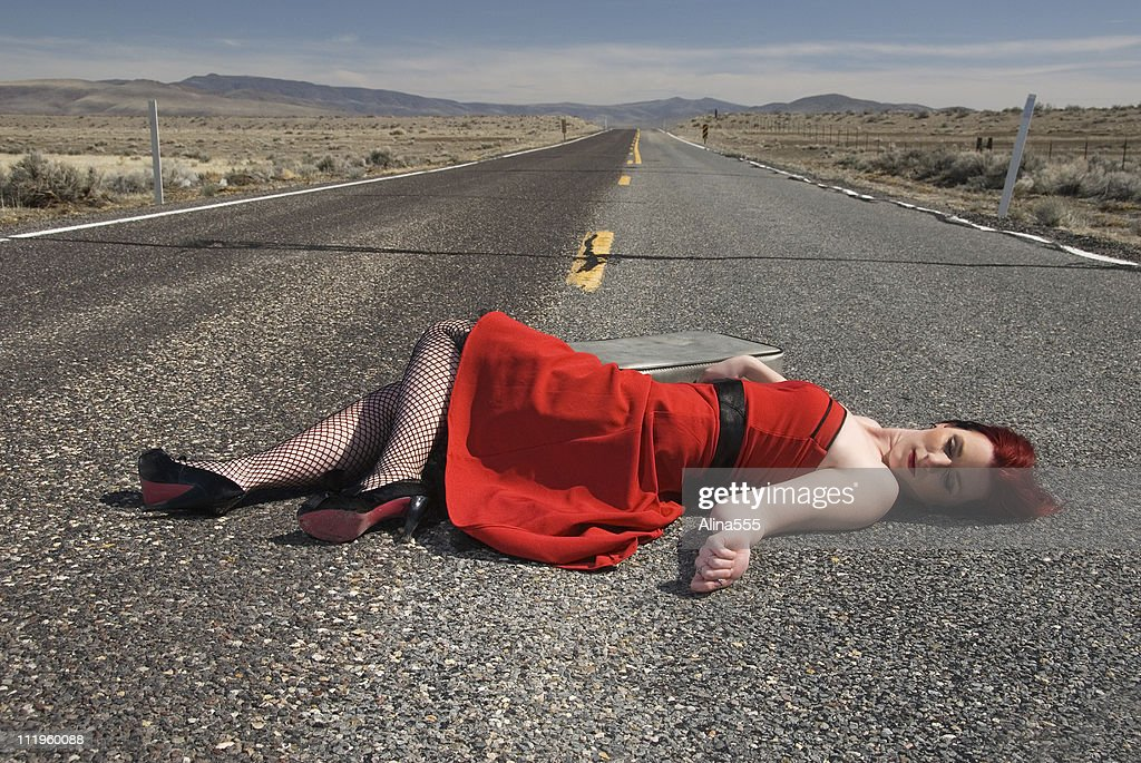 Young woman with is laying lifelessly  on highway : Stock Photo