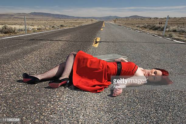 young woman with is laying lifelessly  on highway - death photos stock photos and pictures